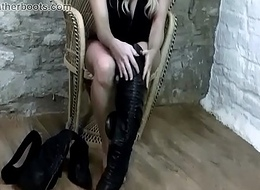 Busty blonde babe puts on leather boots